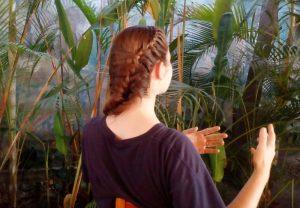 Gebärde vor Palmenwand